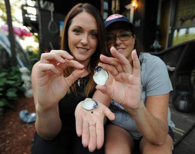 Lisa McGrath, right, and her daughter, Lindsey, discovered two pearls in a quahog while they were raking for the shellfish in Buzzards Bay.