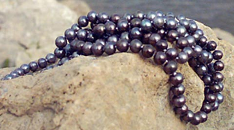 black freshwater pearls necklaces on a rock