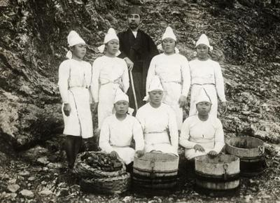 Female pearl divers next to Kokichi Mikimoto, inventor of cultivating pearls. Japan, 1921.Nationaal Archief | Wikimedia Commons